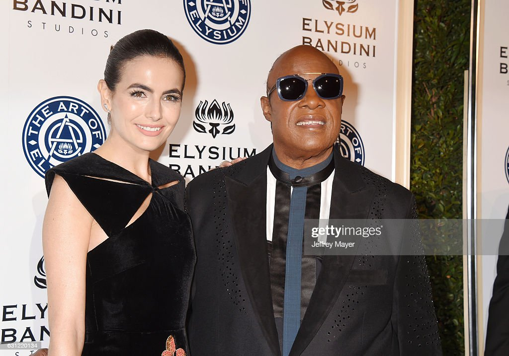 Actress Camilla Belle (L) and musician Stevie Wonder arrive at The Art of Elysium presents Stevie Wonder's HEAVEN - Celebrating the 10th Anniversary at Red Studios on January 7, 2017 in Los Angeles, California.