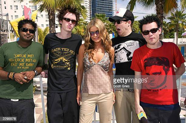 Actress Carmen Electra stands backstage with pop punk band Sum 41 during a taping for MTV Spring Break 2003 at the Surfcomber Hotel March 12 2003 in...