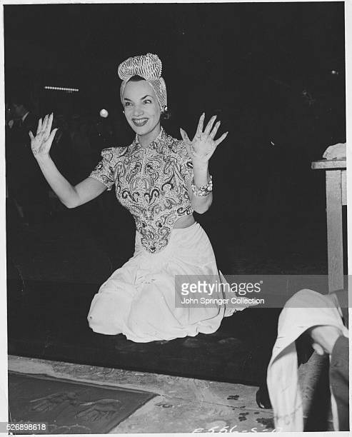 Actress Carmen Miranda shows her cement covered hands after making her mark on the sidewalk