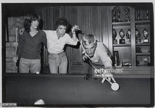 Actress Carol Burnett jokes around with her daughter Carrie while her husband Joseph sets up a shot on the pool table