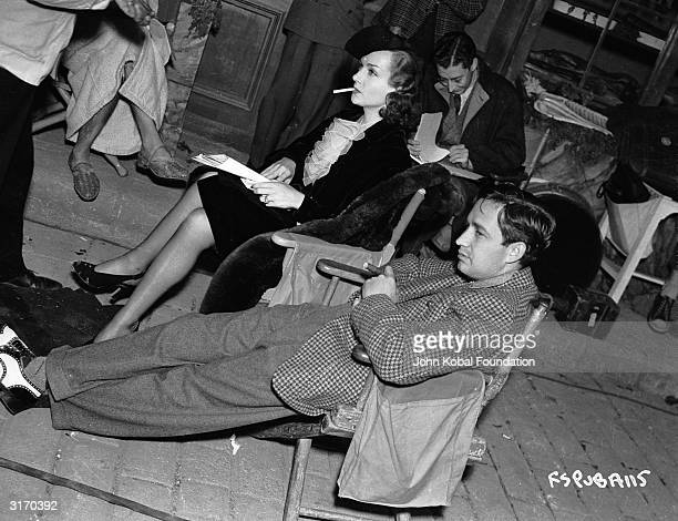 Actress Carole Lombard sitting with director Mervyn LeRoy on the set of 'Fools For Scandal'