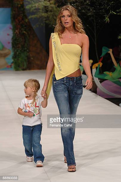 Actress Caroline Bittencourt and daughter Isabelle walk down the runway during the Natal dos Sonhos fashion presentation during the PreaPorter...