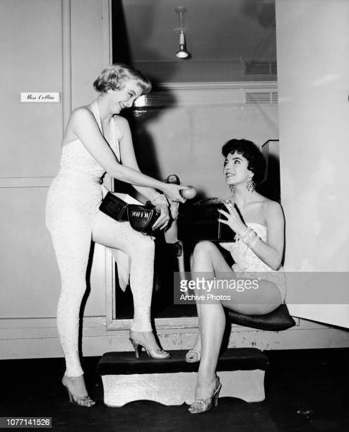 Actress Carolyn Jones offers Joan Collins, her co-star in the MGM film 'The Opposite Sex', a piece of fruit from her lunchbox on the set of the film,...