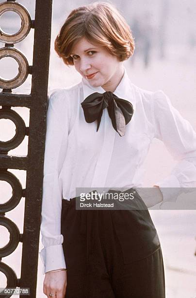 Actress Carrie Fisher leaning against metal gate