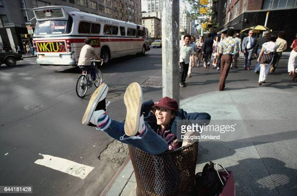 Actress Carrie Fisher sits in a garbage can on a New York street corner