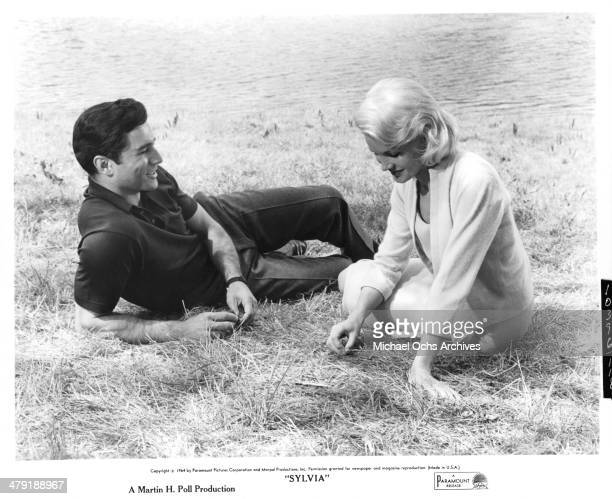 Actress Carroll Baker and actor George Maharis talk in the grass in a scene from the Paramount Pictures movie 'Sylvia' circa 1965