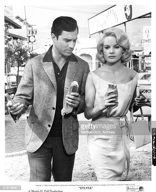 Actress Carroll Baker and actor George Maharis walks holding hot dogs in a scene from the Paramount Pictures movie Sylvia circa 1965