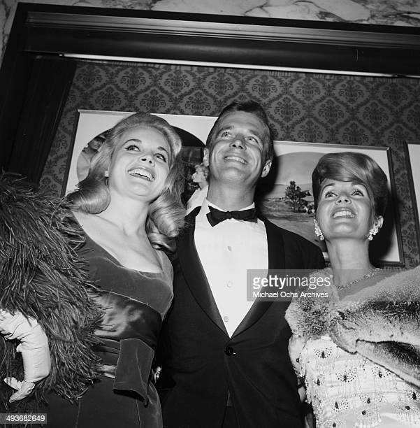 Actress Carroll Baker poses with actor George Peppard and actress Debbie Reynolds during the premier of How the West Was Won in Los Angeles California