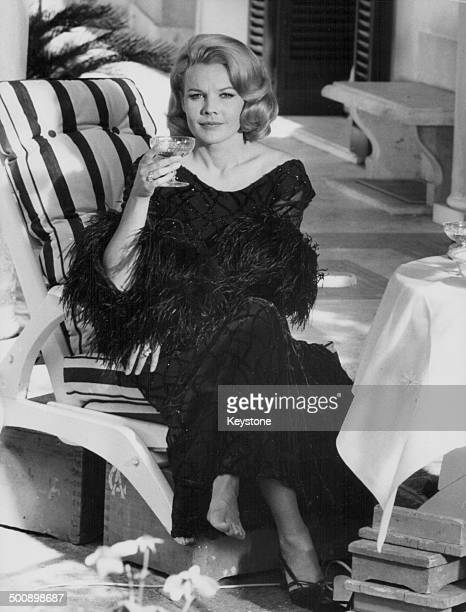Actress Carroll Baker relaxing on a sun lounger with a drink on location to shoot the movie 'Paranoia' Rome 25th July 1968