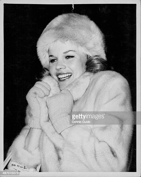 Actress Carroll Baker wearing a fur hat and coat arriving at London Airport to perform a play in London January 3rd 1963