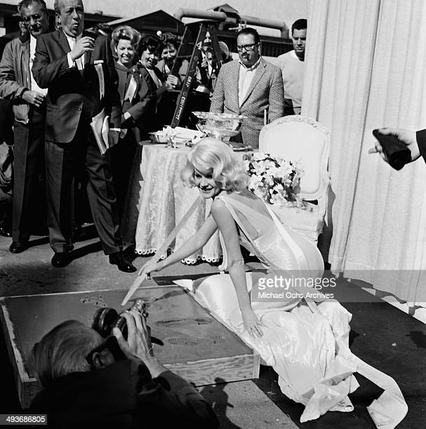 Actress Carroll Baker writes her name in cement in Los Angeles California
