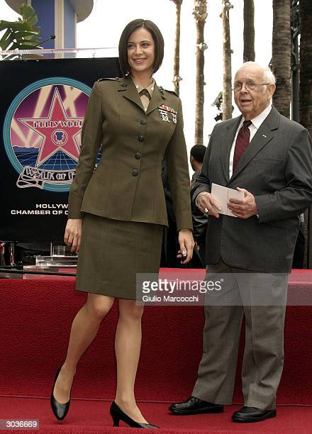 Actress Catherine Bell stands near actor Johnny Grant as they attend a Star On The Walk Of Fame ceremony for Donald P Bellisario March 2 2004 in...
