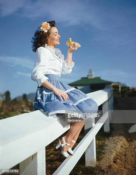 Actress Catherine McLeod holds a small duckling while seated on a fence
