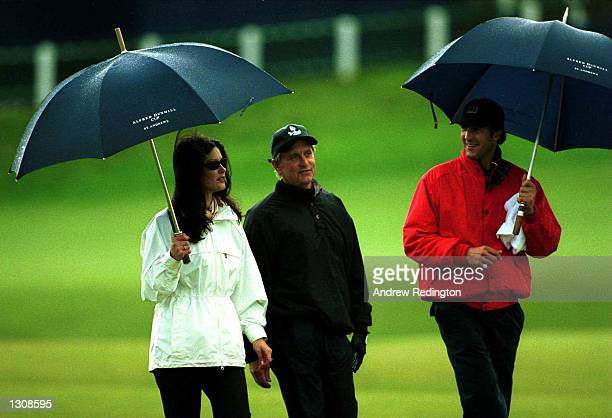 Actress Catherine ZetaJones actor Michael Douglas and Robert Baker shelter themselves from the rain during the ProAm of the Alfred Dunhill Cup played...
