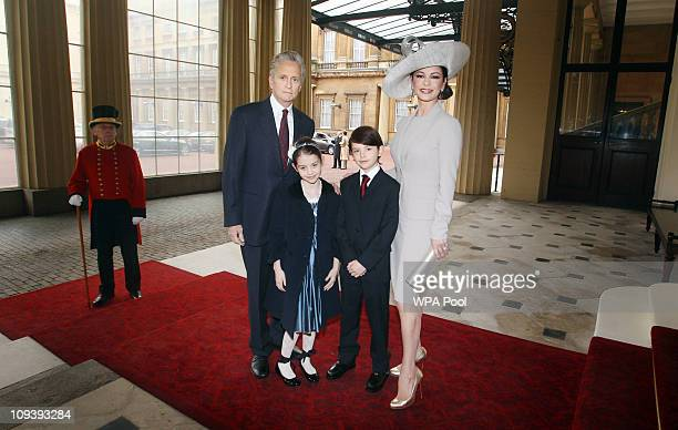 Actress Catherine ZetaJones arrives with her husband actor Michael Douglas and their children Dylan and Carys Douglas to attend a Royal Investiture...