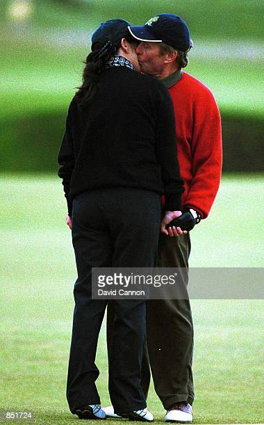 Actress Catherine ZetaJones kisses her fiance Michael Douglas on the 10th hole before the ProAm of the Alfred Dunhill Cup on the Old Course October...
