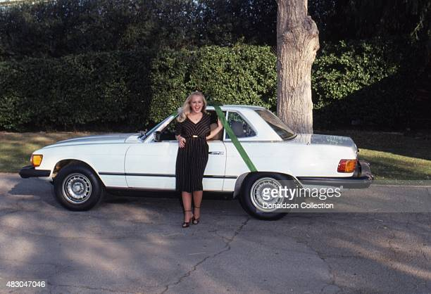 Actress Charlene Tilton poses for a portrait with her Christmas present a white Mercedes from her business manager Jon Mercedes in December 1979 in...