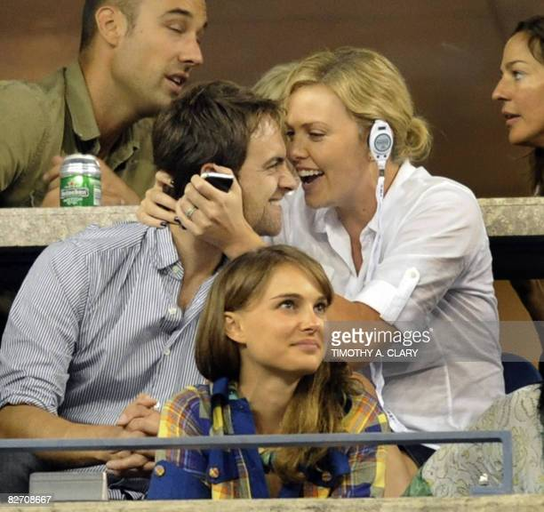 Actress Charlize Theron and actor Stuart Townsend watch the match between Jelena Jankovic of Serbia during her finals match to Serena Williams of the...