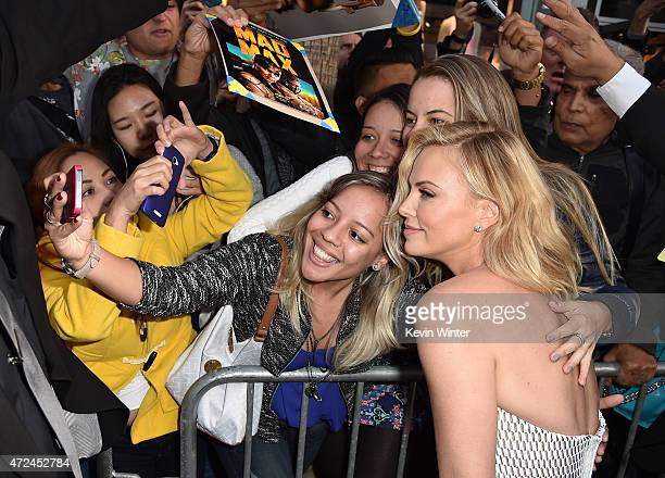 "Actress Charlize Theron poses for a selfie with fans as she attends the premiere of Warner Bros. Pictures' ""Mad Max: Fury Road"" at TCL Chinese..."
