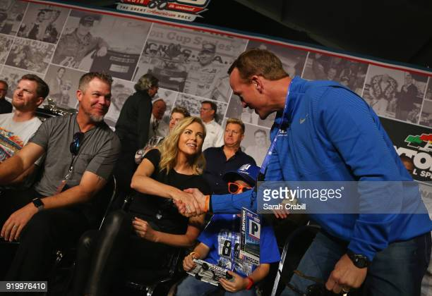 Actress Charlize Theron shakes hands with twotime Super Bowl winning quarterback Peyton Manning during the drivers meeting for the Monster Energy...
