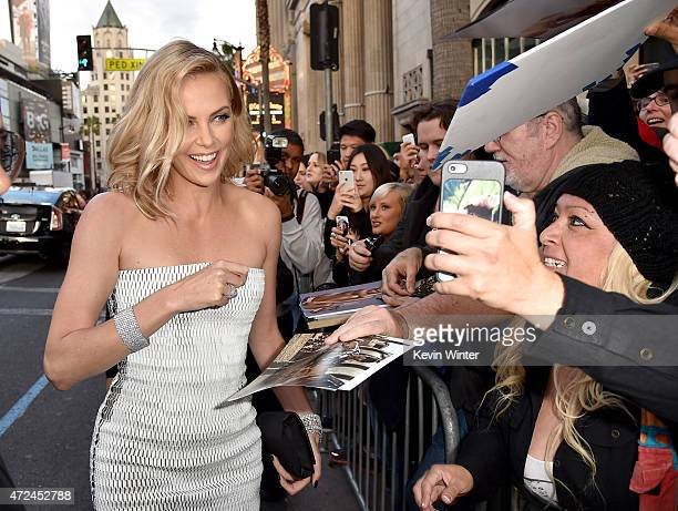 "Actress Charlize Theron signs autographs as she attends the premiere of Warner Bros. Pictures' ""Mad Max: Fury Road"" at TCL Chinese Theatre on May 7,..."