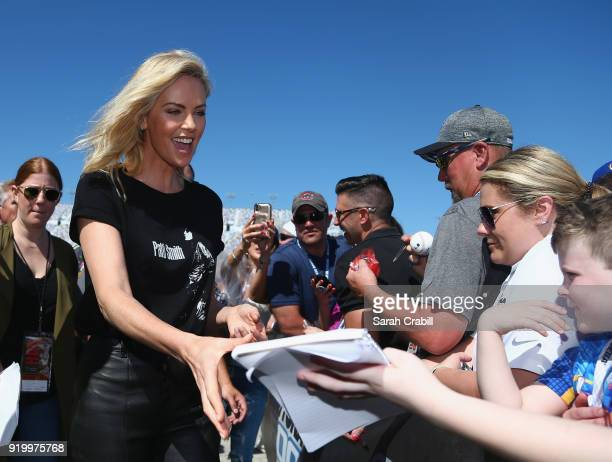 Actress Charlize Theron signs autographs prior to the start of the Monster Energy NASCAR Cup Series 60th Annual Daytona 500 at Daytona International...