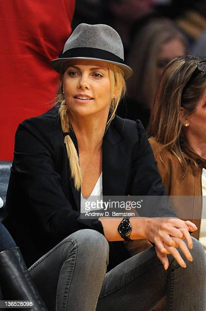 Actress Charlize Theron watches the game between the Golden State Warriors and the Los Angeles Lakers at Staples Center on January 6 2012 in Los...