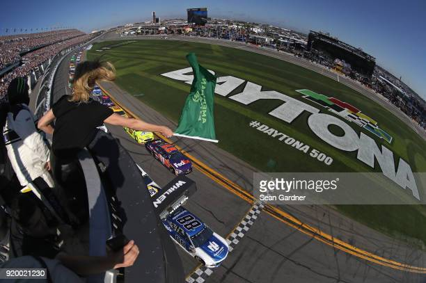 Actress Charlize Theron waves the green flag to start the Monster Energy NASCAR Cup Series 60th Annual Daytona 500 at Daytona International Speedway...