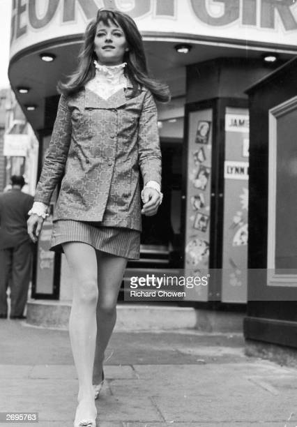 Actress Charlotte Rampling wears a highcollared Edwardianstyle shirt under a double breasted jacket Her miniskirt is in contrasting stripes