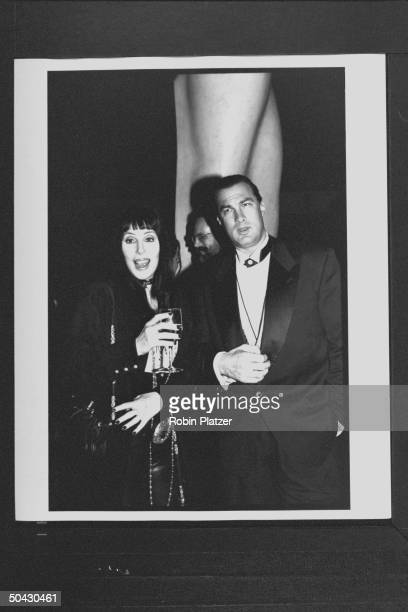 Actress Cher holding drink while posing w actor Steven Seagal at the 12th annual Council of Fashion Designers of America Awards ceremony at Lincoln...