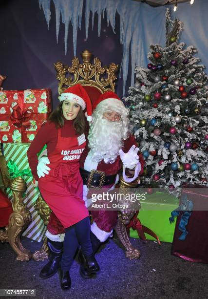 Actress Christina DeRosa poses with Santa Claus at the Los Angeles Mission Christmas On Skid Row held at Los Angeles Mission on December 21 2018 in...