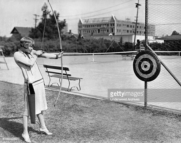 Actress Claire Windsor takes aim with a bow and arrow at the MGM lot Hollywood California 1927