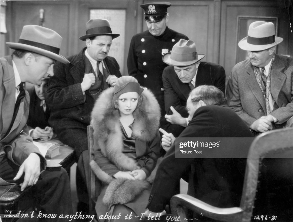Actress Clara Bow (1905- 1965) is questioned by police in a scene from the film 'No Limit', directed by Frank Tuttle for Paramount.