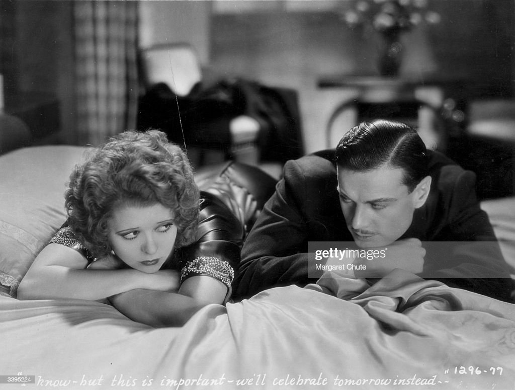 Actress Clara Bow (1905-1965) pouts beside Norman Foster (1900-1976), in a bedroom scene from the film 'No Limit', directed by Frank Tuttle for Paramount.