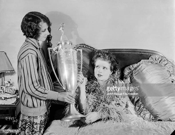 Actress Clara Bow sitting up in bed and being handed a trophy in a scene from the film 'HoopLa' for 20th Century Fox 1933