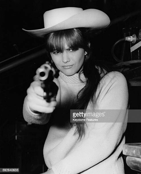 Actress Claudia Cardinale wearing a cowboy hat and pointing a gun at the camera on the set of the film 'Circus World' at Pinewood Studios London...