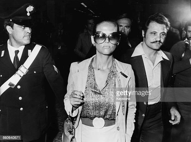 Actress Claudia Cardinale wearing sunglasses as she is escorted to court, where director Pasquale Squitieri is appearing on charges of firing shots...