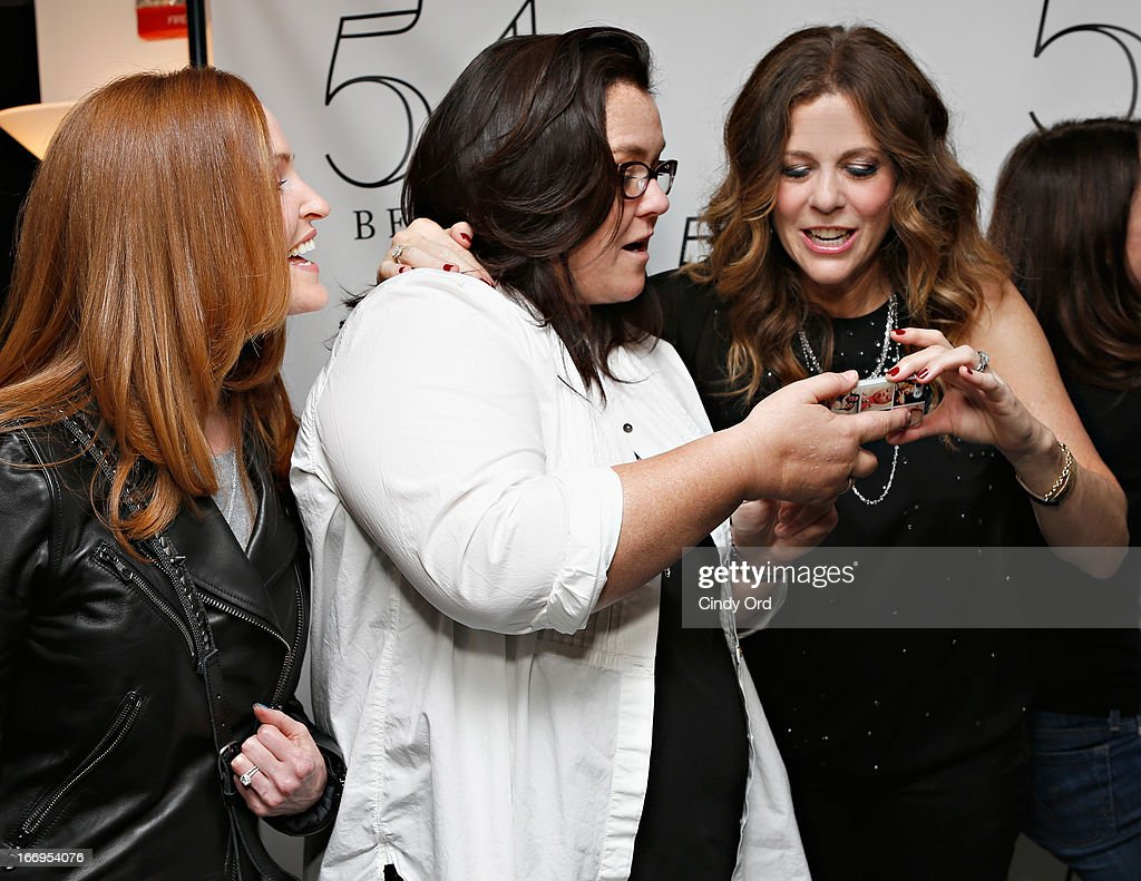 Actress/ comedianRosie O'Donnell (C) and wife Michelle Rounds (L) share photos of their children backstage with actress/ singer Rita Wilson following her performance at 54 Below on April 18, 2013 in New York City.