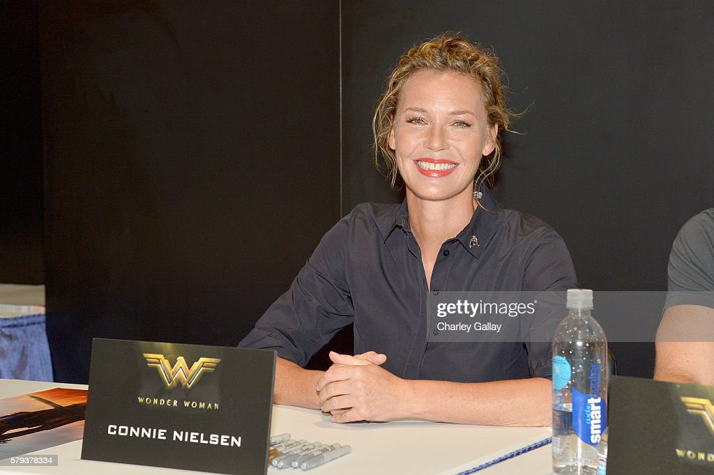 Actress Connie Nielsen from the 2017 feature film Wonder Woman signs autographs for fans in DC's 2016 San Diego Comic-Con booth at San Diego Convention Center on July 23, 2016 in San Diego, California.