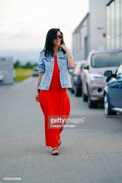 Actress Cosmina Pasarin wears a blue denim jacket a red dress earrings sunglasses during Feeric Fashion Week 2018 on July 20 2018 in Sibiu Romania