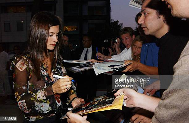 "Actress Courteney Cox Arquette signs autographs prior to the premiere of ""Serving Sara"" at the Samuel Goldwyn Theater on August 20, 2002 in Beverly..."