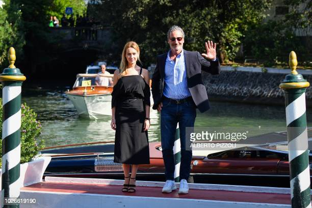 Actress Cristiana Capotondi and US yachtsman and professional sailor Paul Cayard pose after they arrived by boat at the pier of the Excelsior Hotel...