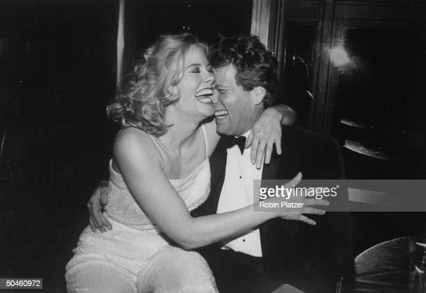 Actress Cybill Shepherd seated on lap of actor Ryan O'Neal at party for movie Chances Are in which both appeared at Rainbow Room
