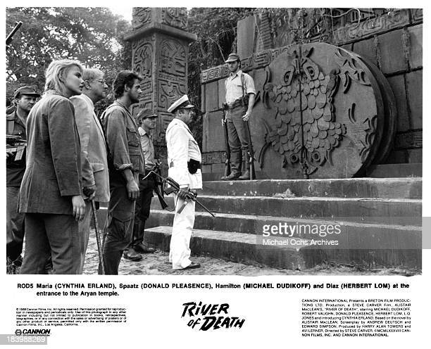 Actress Cynthia Erland actors Donald Pleasence Michael Dudikoff and Herbert Lom on set of the Cannon Films movie River of Death in 1989