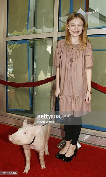 Actress Dakota Fanning poses with Wilbur at the Los Angeles premiere of Paramount's Charlotte's Web at the ArcLight Theatre December 10 2006 in Los...