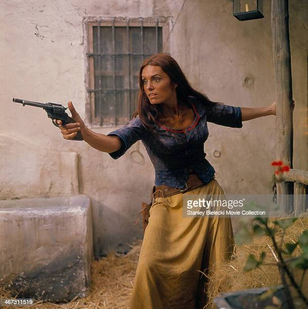 Actress Daliah Lavi pointing a gun in a scene from the film 'Catlow' 1971