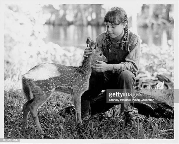 Actress Dana Hill with a fawn in a scene from the movie 'Cross Creek' 1983
