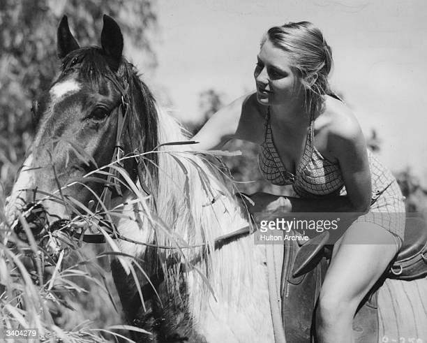 Actress Daphne Campbell leans forward to pat her horse in a scene from the Ealing Studios film 'The Overlanders'