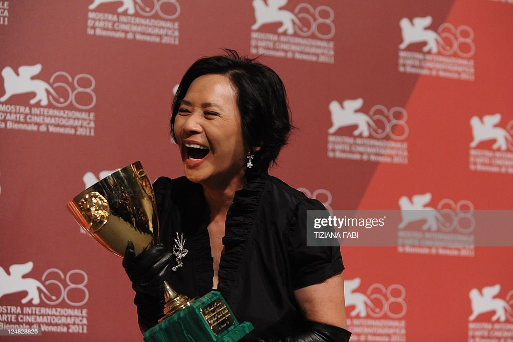 Actress Deanie Yip poses with the Volpi Cup for best actress she received for 'Tao Jie (A simple life)' during a photocall following the award ceremony at the 68th Venice Film Festival on September 10, 2011 at Venice Lido.