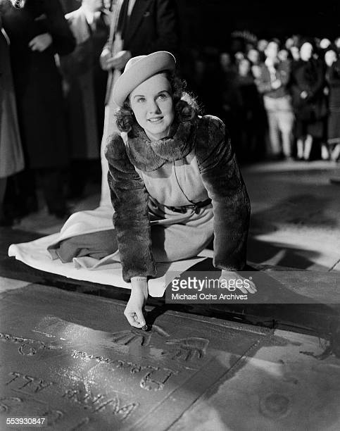 Actress Deanna Durbin poses after making a hand print in cement in front of Grauman's Chinese Theater in Los Angeles, California.